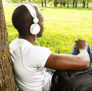 Young african american man in white shirt listens headphones in a park