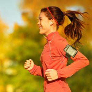 Woman runner running in fall autumn forest