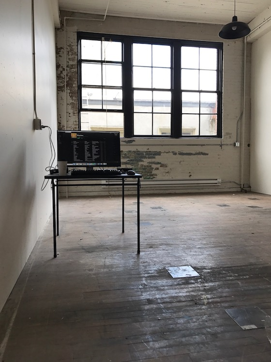 a very bare room with a large window, a desk, and a laptop -- no chair yet -- that will serve as the new Portland Book Riot office