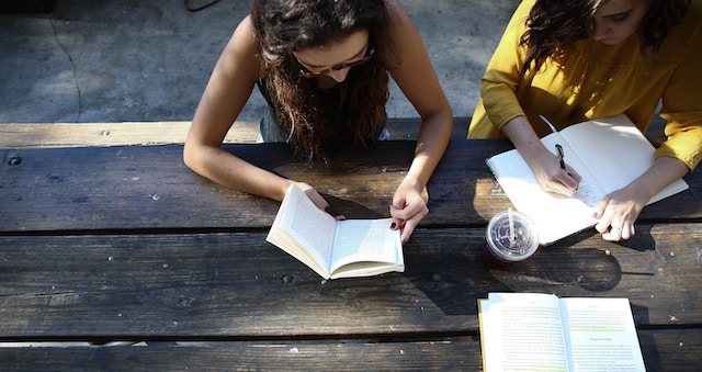 image of two people reading at a wooden table