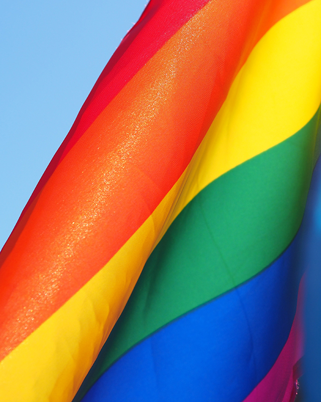 a close up of a rainbow flag waving in a breeze