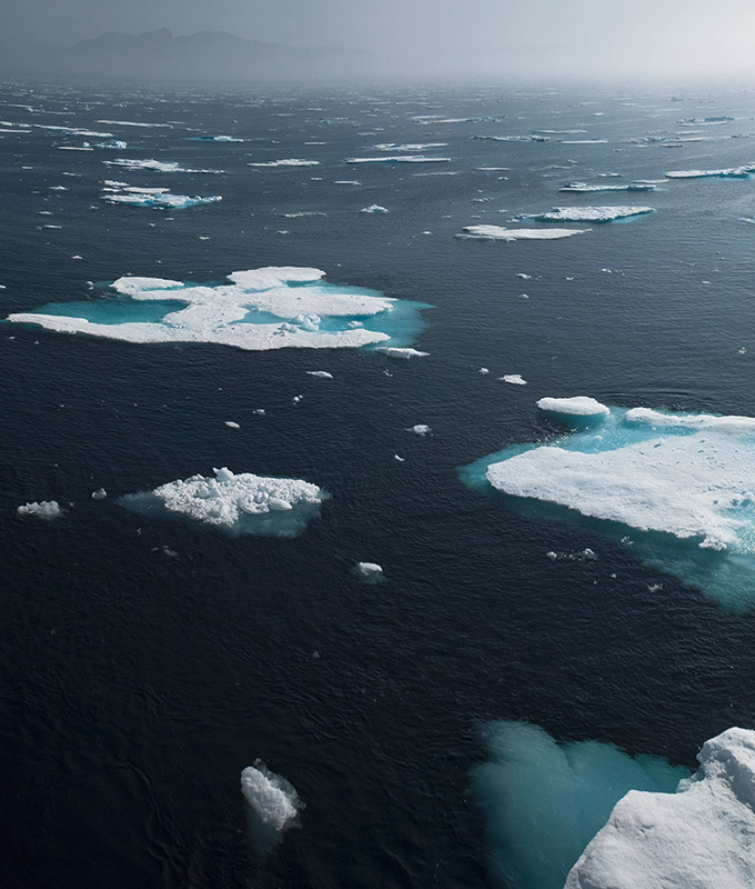a photo of ice floes on a very blue sea