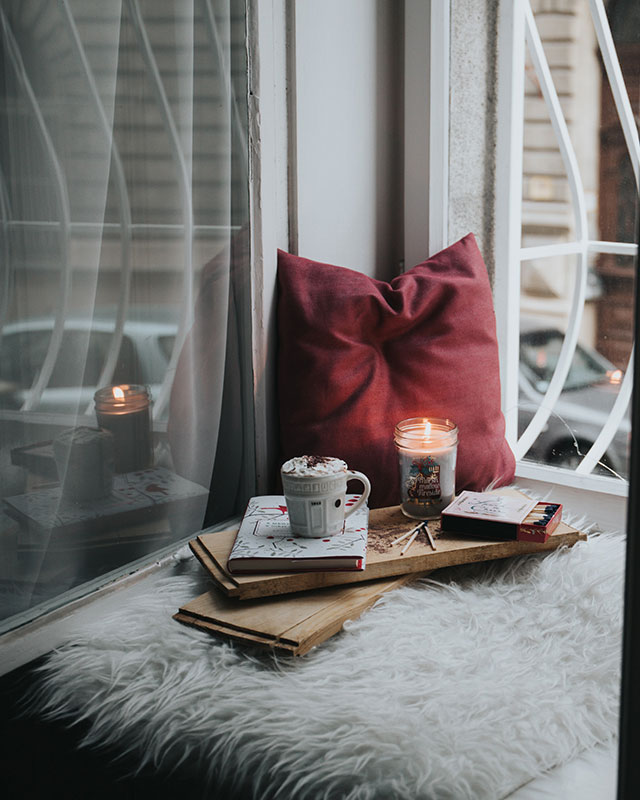 a photo of a reading nook in a window. there is a fluffy white pillow, and all the window trim is white as well. a crimson pillow sits in a corner, and there is a small book onto of a wooden rest, with a cup of hot chocolate on top and a glowing candle next to it.