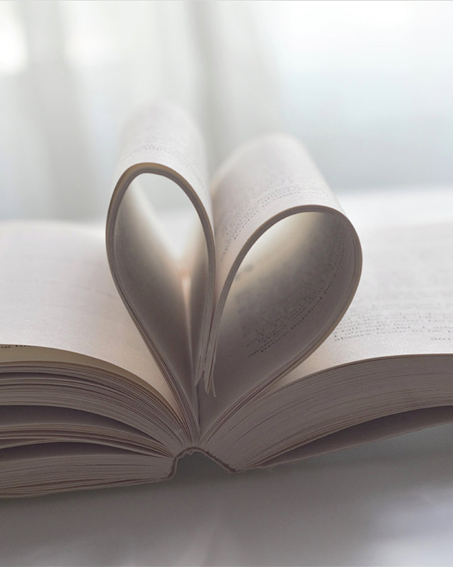 a close-up photograph of an open book with central pages bent into a heart shape, against a white background