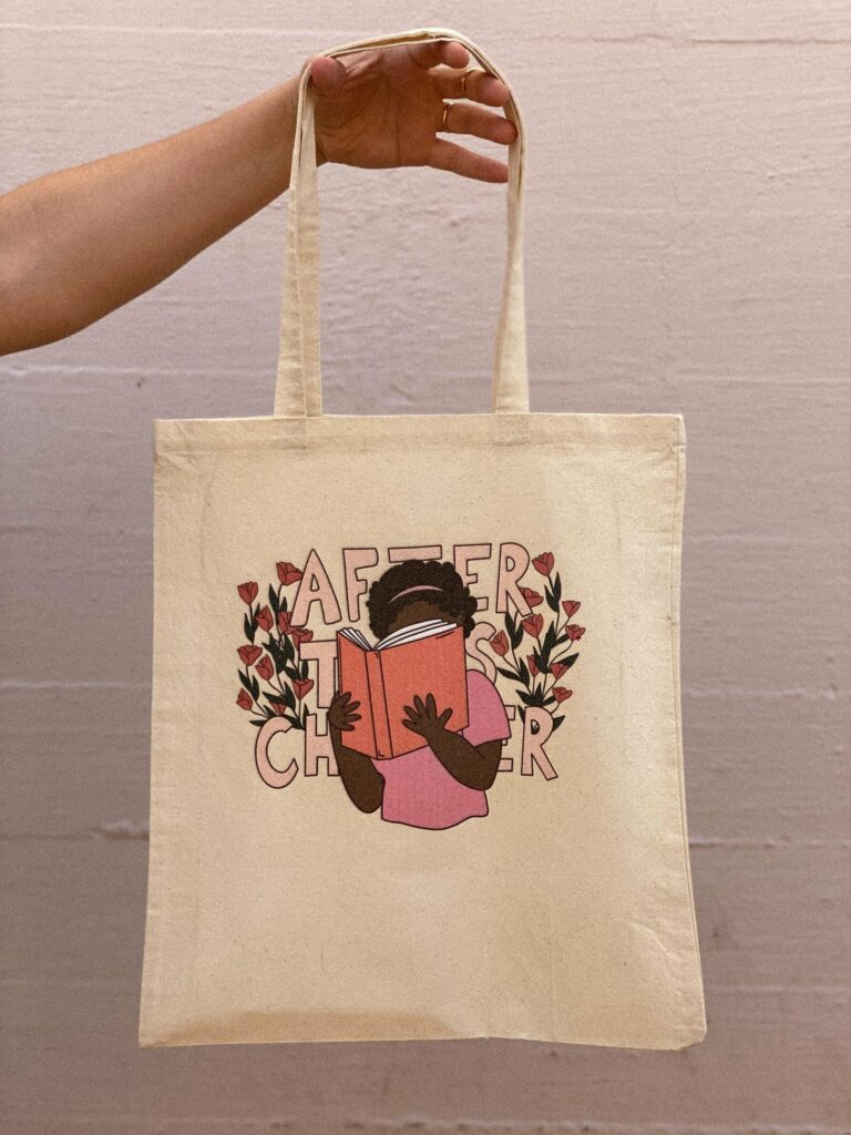 """Image of a canvas tote bag, featuring a black girl reading a book. Behind her image are the words """"after this chapter."""""""
