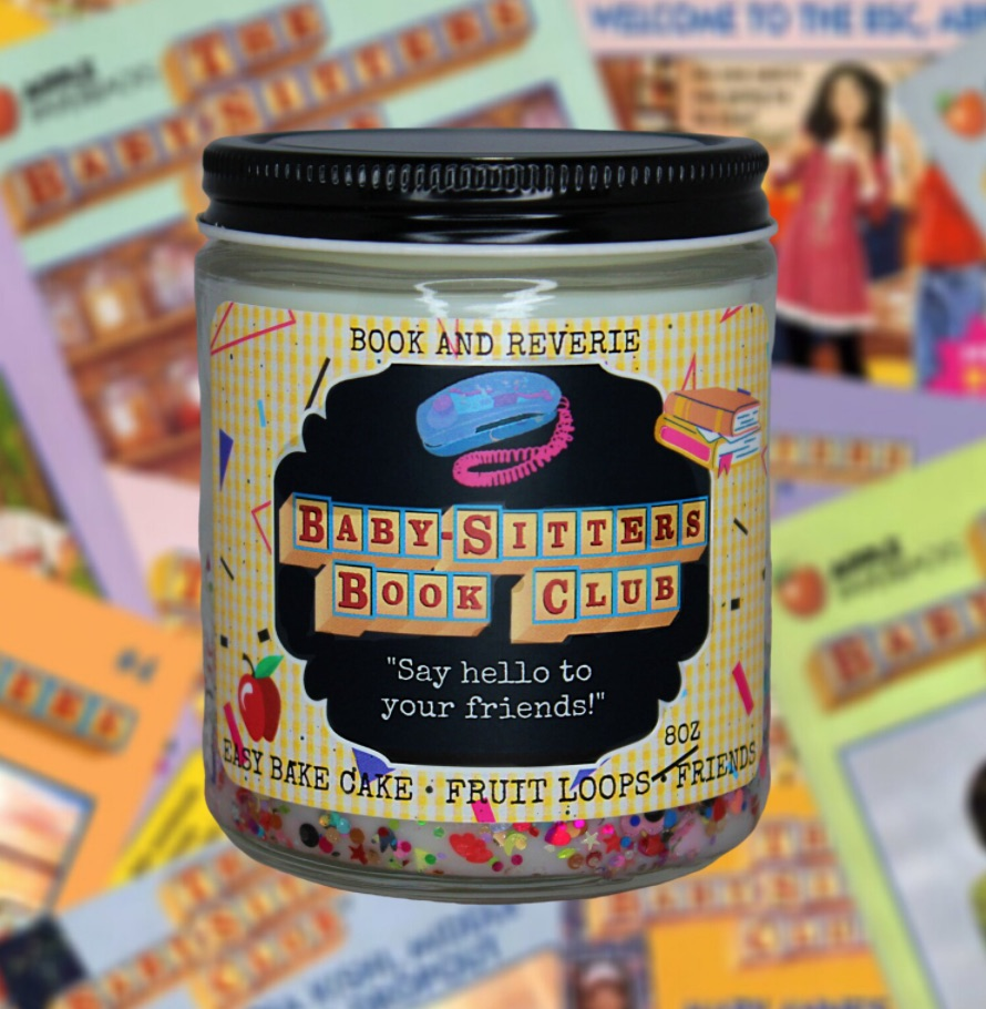 """Image of a candle with a label featuring """"Baby-Sitters Book Club,"""" as phone, books, and the description of the candle's scent."""