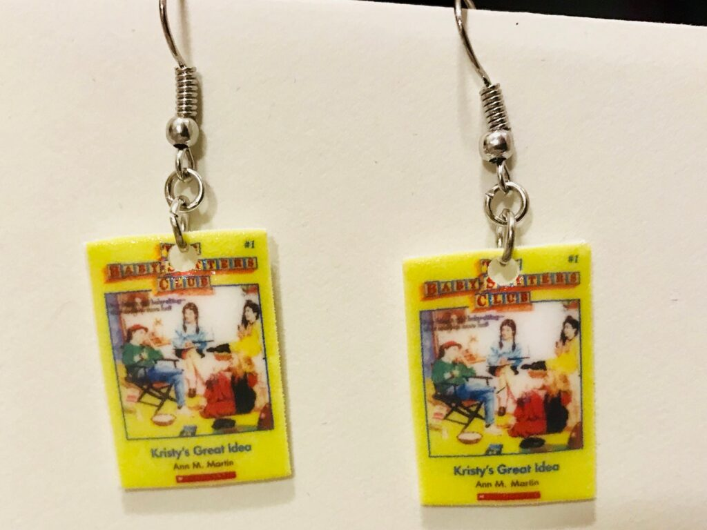 Earrings featuring mini covers of Kristy's Great Idea