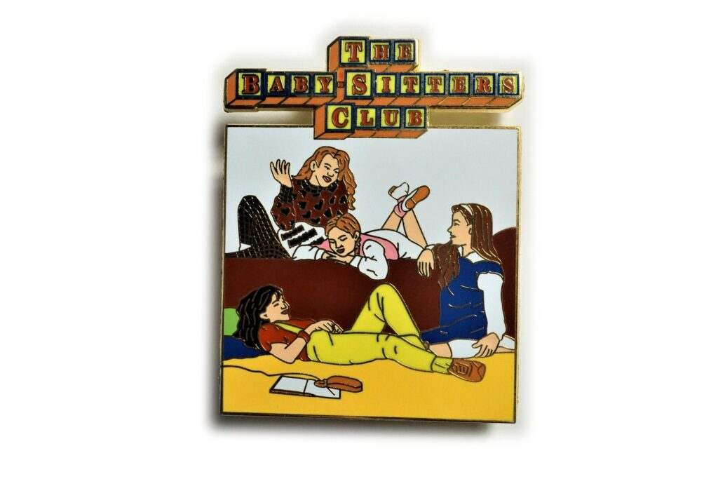 Image of an enamel pin featuring the cover of the first BSC book.